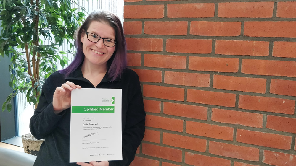 Photo of Daria with her certificate against a red wall and green plant.